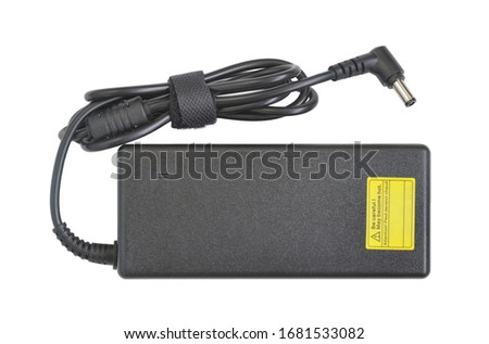 Power adapter. AC to DC converter for laptop. Black plastic rectangular box with cable and L-shaped connector 5.5 by 2.5 mm. Top view. Isolated on white.