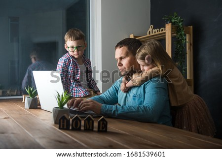 Work from home. Man works on laptop with children playing around. Family together #1681539601
