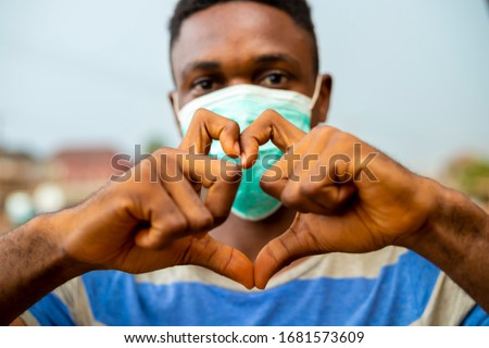young handsome african nigerian man wore face mask preventing, prevent, prevented himself from the outbreak in his society and did a love sign. #1681573609