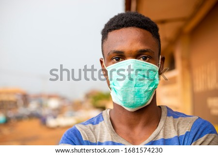 young handsome african man wore face mask preventing, prevent, prevented himself from the outbreak in his society. #1681574230