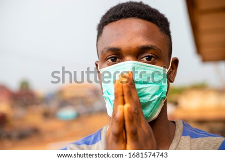 young handsome african man wore face mask preventing, prevent, prevented himself from the outbreak in his society and pleading that people show wear face mask. #1681574743