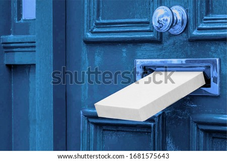 Sending a Gift In The Post.Postal white box the parcel is delivered through the parcel door opening.White post box and old aged grunge blue wooden door. #1681575643