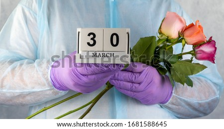 doctor with a bouquet of flowers in his hands. medical worker in surgical gown and medical gloves. Close- up of a bouquet of beautiful roses. National Doctor's Day March 30. recovery from coronavirus.