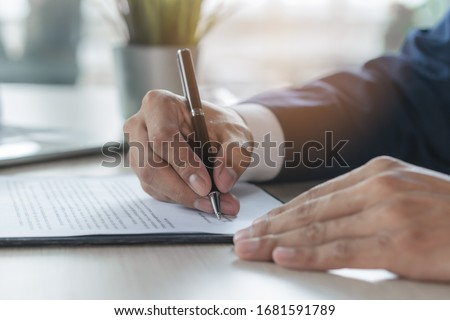 Contract document official. Close up person signing his signature to agreement document to guarantee financial loan.