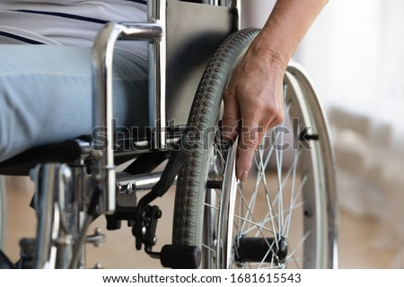 Close up of senior handicapped woman sit in wheelchair taken care of in hospital or home, mature disabled old lady grandmother in invalid carriage or wheel chair, elderly disability concept Royalty-Free Stock Photo #1681615543