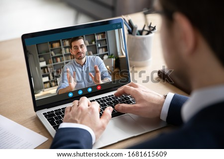 Back view of businessman talk with male business partner using video call on laptop discuss work project online, male client talk with colleague or coworker, speak on webcam conference on computer #1681615609