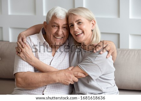Head shot portrait older wife and husband with healthy toothy smiles hugging, looking at camera, sitting on cozy sofa at home, happy adult middle-aged daughter embracing mature father, family photo #1681618636