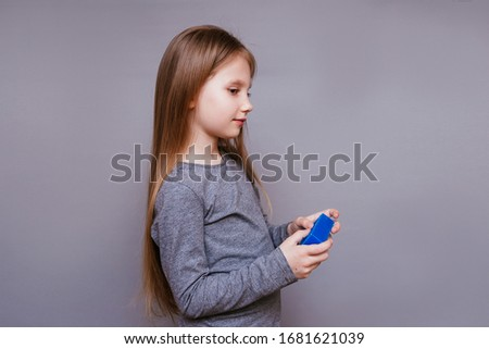 Little girl on a gray background with soap in the hands #1681621039