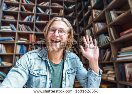 Cheerful male blogger influencer waving hand looking at camera recording video blog concept in library, happy young man laughing face shooting vlog for social media channel making video call concept. #1681626556