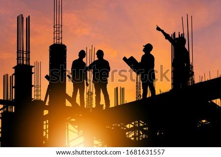 Silhouette of Engineer and worker on building site, construction site at sunset in evening time. Royalty-Free Stock Photo #1681631557
