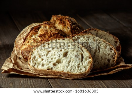 Bread, traditional sourdough bread cut into slices on a rustic wooden background. Concept of traditional leavened bread baking methods. Healthy food. #1681636303
