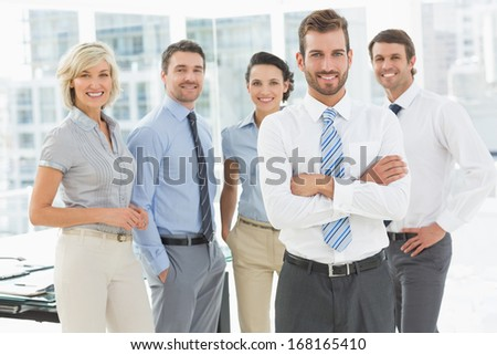 Portrait of a confident business team standing together in a bright office #168165410