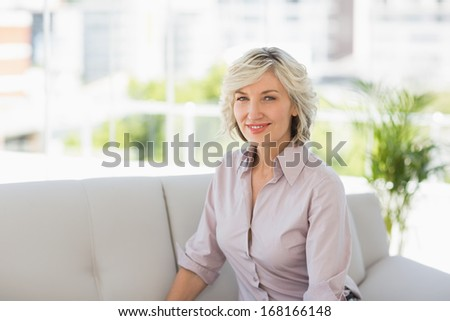 Portrait of a mature woman sitting on sofa in the house #168166148
