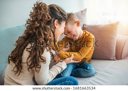 The kind of love that can't be described, only felt. Mother and her child, tickling, kidding and having fun in the couch, with spontaneous smiles. Loving my son  Royalty-Free Stock Photo #1681663534