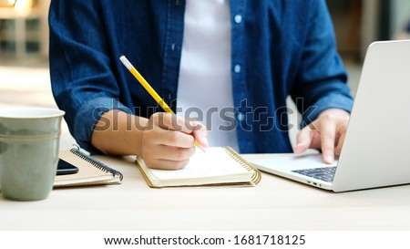 Online class, Student writing on notebook while study at home, Adult man doing online lesson by using laptop computer, Digital technology education, Work from home Royalty-Free Stock Photo #1681718125