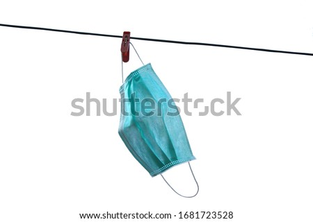 The medical disposable face mask is hanging on the rope on white background Royalty-Free Stock Photo #1681723528
