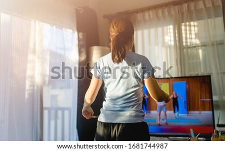 Video streaming Stay home.home fitness workout class live streaming online.Asian woman doing strength training cardio aerobic dance exercises watching videos on a smart tv in the living room at home. #1681744987