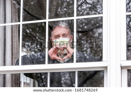 Man wearing mask making heart symbol with hands at the window #1681748269