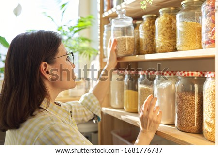 Food storage, wooden shelf in pantry with grain products in storage jars. Woman taking food for cooking #1681776787