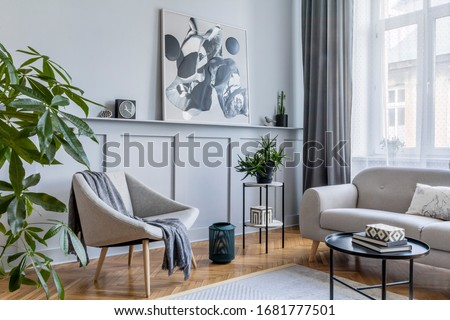 Stylish scandinavian home interior of living room with design gray sofa, armchair, marble stool, black coffee table, modern paintings, decoration, plant and elegant personal accessories in home decor. #1681777501