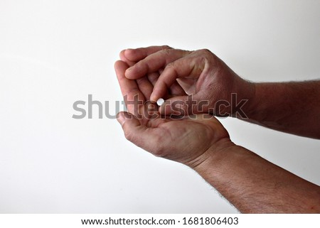 homeopathy pills in the hands of a man, white background #1681806403