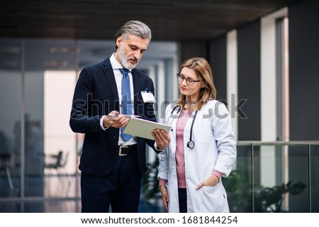 Pharmaceutical sales representative with tablet talking to doctor. Royalty-Free Stock Photo #1681844254