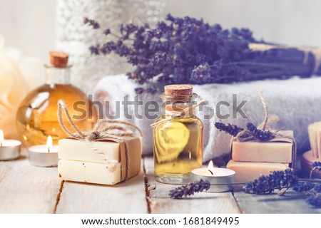 Concept of spa with natural organic oil. Moisturizing skin care and aromatherapy. Gentle body treatment. Handmade soap. Atmosphere of harmony, relax. Wooden background, lavender flowers, candle Royalty-Free Stock Photo #1681849495