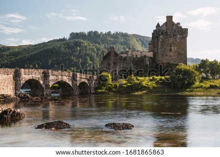 Old castle with a bridge with arcs and a river in a sunny day in Scotland, Eilean Donan Castle