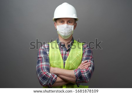 Worker man wearing hygienic mask and protective hard hat. Young engineer worker wear a white helmet and medical face mask. Coronavirus Hygiene, safety concept #1681878109