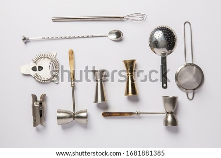 Flat lay composition with bartender iron tools, such as cocktail shaker, jigger, mixing glass, stirring spoon. Background is white. Royalty-Free Stock Photo #1681881385