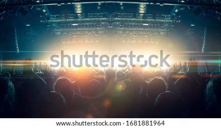 Concert crowd point of view inside a large concert hall during a music festival, the lit stage is visible. Royalty-Free Stock Photo #1681881964