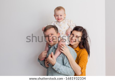 happy european family with baby smiling laughs at home on a white background. Millennials are young modern parents. Positive clothes. The child sits on his shoulders. Dad mom daughter. Full life style #1681932334