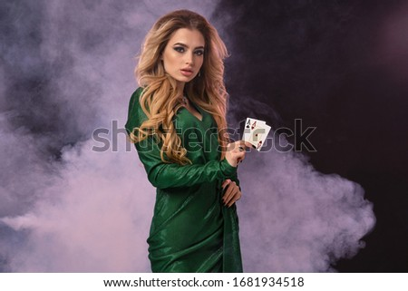 Blonde model with make-up, in green dress and jewelry. Put hand on hip, showing two aces, posing on black smoky background. Poker, casino. Close-up Royalty-Free Stock Photo #1681934518