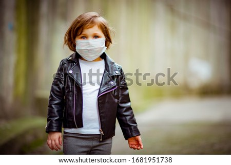 little girl on a walk in a medical mask #1681951738