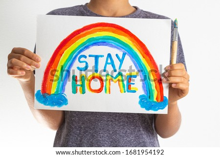 Kid holding drawing picture with rainbow with words Stay at home. Social media campaign for coronavirus prevention