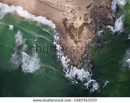 Uruguay, Punta del diablo. Vista aérea de la playa y el mar. Las olas rompen contra la arena y rocas, el agua es verde y oscura.  Uruguay tiene estas playas salvajes y solitarias. #1681961059