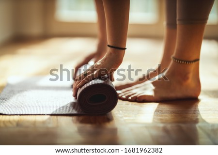 Close up of a womans hands is rolling up exercise mat and preparing to doing yoga. She is exercising on floor mat in morning sunshine at home. #1681962382