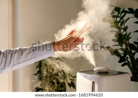 Woman holds hand over steam aroma oil diffuser on the table at home, steam from humidifier. Humidification of air in apartment during the period of self-isolation due to coronavirus pandemic #1681994620