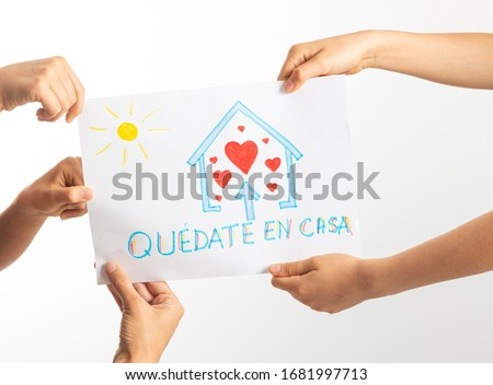 Quarantine at home during coronavirus pandemic in Spain. Family holding drawing picture with spanish words Quedate en casa - Stay at home. Social media campaign for coronavirus prevention #1681997713