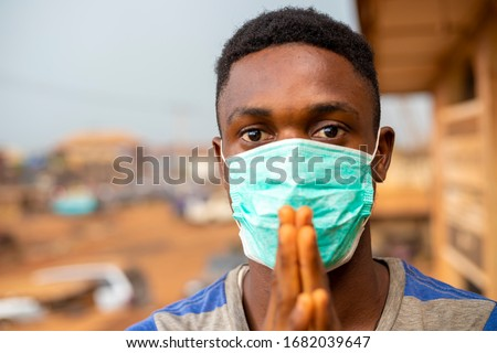 young handsome african man wore face mask preventing, prevent, prevented himself from the outbreak in his society and pleading that people show wear face mask. #1682039647