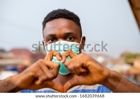 young handsome african nigerian man wore face mask preventing, prevent, prevented himself from the outbreak in his society and did a love sign. #1682039668