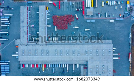 Aerial top down view of the large logistics park with warehouse, loading hub with semi trucks with cargo trailers standing at the ramps for load/unload goods #1682073349