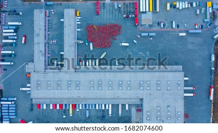 Aerial top down view of the large logistics park with warehouse, loading hub with semi trucks with cargo trailers standing at the ramps for load/unload goods #1682074600