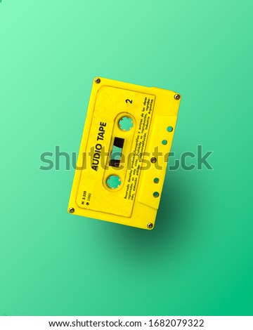Yellow audio tape on a green background, retro cassette of the eighties