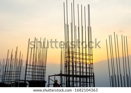 Steel reinforce in concrete column.Steel grid on the construction site.Reinforcement of concrete work. Using steel wire for securing steel bars with wire rod for reinforcement of concrete at sunset #1682104363