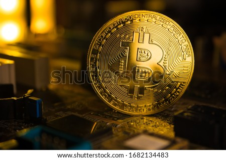 A golden coin with bitcoin symbol on a mainboard. #1682134483