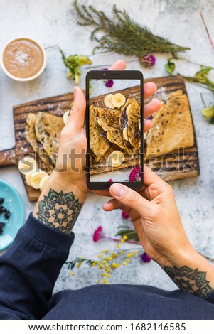 Woman hands make photo of french crepes - thin fried sweet pancakes with phone. Smartphone food photography picture.