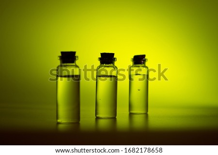 Three glass corked bottles filled with liquid. Background for science and medicine. Virus vaccine. #1682178658