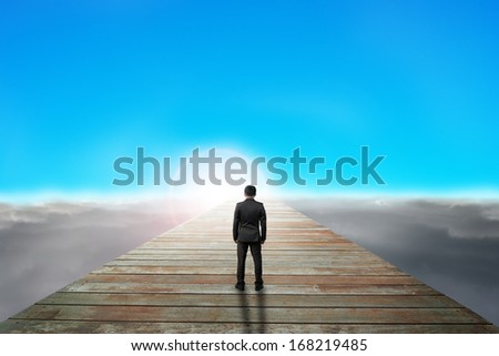 businessman standing on wooden path looking sunrise with cloudy below and blue sky #168219485