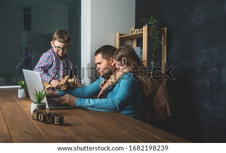 Work from home on laptop. Father and children boy and girl sitting on the table.  #1682198239